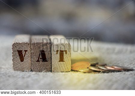 Wooden Blocks With Vat And Money Coins. Taxes Fees Vat Finance Business Concept
