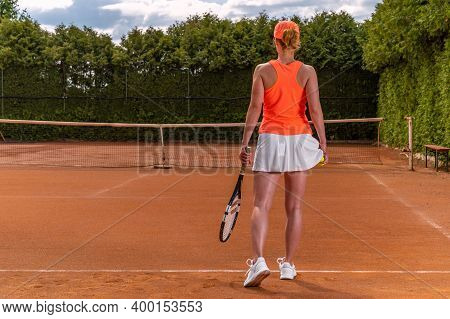 Tennis Ball In A Womans Hand In A Skirt On A Tennis Court. Preparation For Serving A Balloon In Tenn