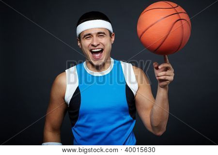 Portrait of laughing guy in sportswear with basket ball on his forefinger looking at camera