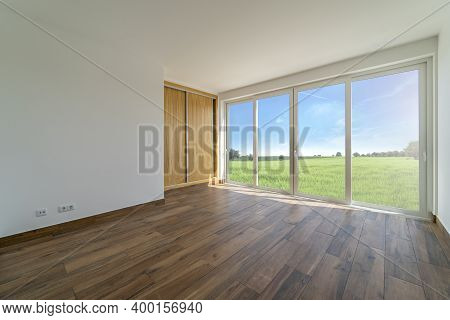 Empty Room With Dark Wooden Floating Laminate Flooring. House Interior, Wide Bedroom Space. New Cout