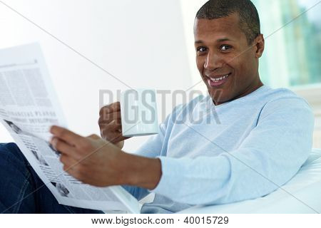 Image of young African man with cup and newspaper looking at camera