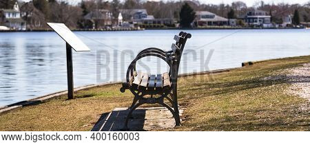 View Of A Wood Bench With Medal Arm Rests Along The Connetquot River In East Islip New York.