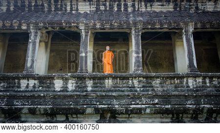 Siem Reap, Cambodia - December 2015: Monk Standing By Stone Columns Of Angkor Wat Ruins. Angkor Wat