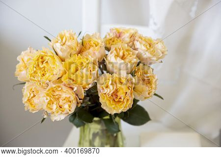 Bouquet Of Orange Roses Candlelight On The White Wooden Chair Next To White Wall. Copy Space