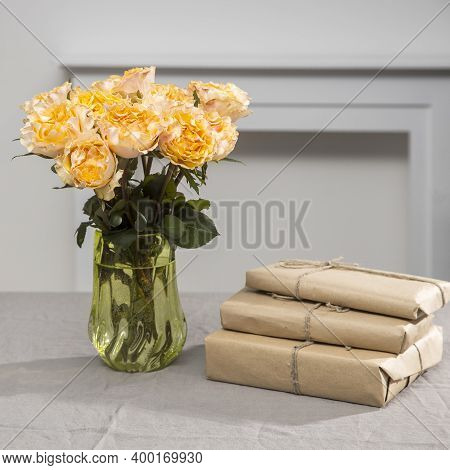 Bouquet Of Orange Roses Candlelight On Grey Tablecloth On The Table Next To White Wall. Square Frame