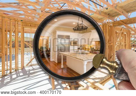 Hand Holding Magnifying Glass Revealing Finished Kitchen Build Over Construction Framing.