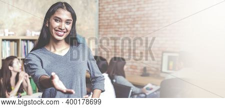 Smiling Young Asian Transgender Employee Extend Handshake Standing At Office With Colleagues Working