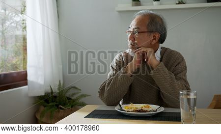 Sad Old Retired Gray Haired Grandpa Asian Man Sitting Alone At Table Desk At Window Boring Stay Home
