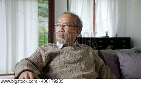 Asian Elderly Senior Male Or Depressed Grandpa At Nursing Home Living Room On Quarantine Looking Out