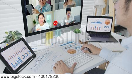 Business Man Talking About Sale Report In Video Conference.asian Team Using Laptop And Tablet Online