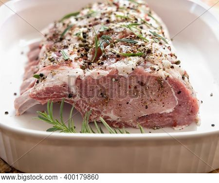 Closeup Of Raw Rack Of Pork With Spices And Rosemary In The White Baking Dish.