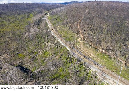 Aerial View Of A Train Running Through And Area Of Forest Regeneration After Bushfire In Dargan In T