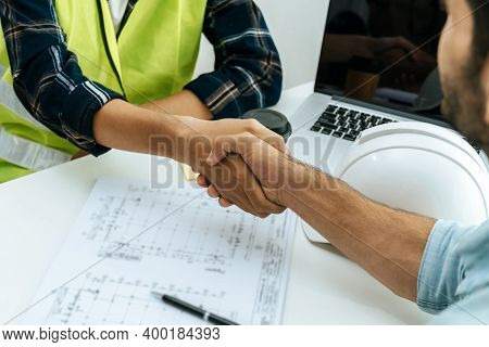Engineer, Architect, Construction Worker Team Hands Shaking After Plan Project Contract On Workplace