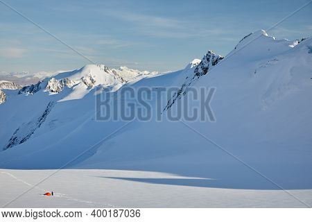 Red tent on the glacier in high mountains
