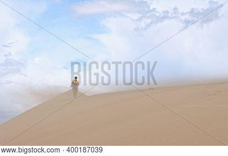 Tourist walking along the edge of the sand dune. Large barkhan in Mongolia sandy dune desert Mongol Els. Govi-Altay, Mongolia.