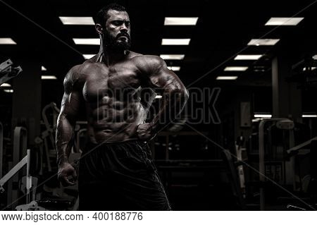 Mighty Strong Athlete Bearded Male With Sport Physique Body In Dark Fitness Gym With Copy Space