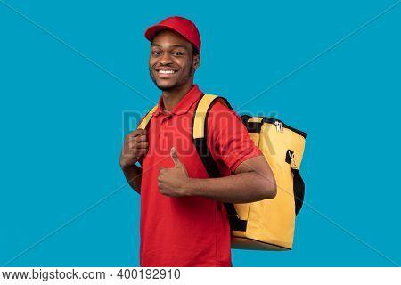 Best Delivery Service Concept. Portrait Of Confident Smiling Black Male Courier Wearing Red Uniform
