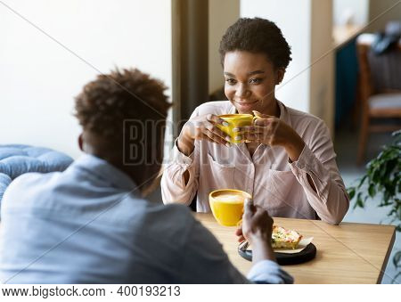 Handsome Black Man With His Girlfriend Enjoying Aromatic Coffee And Having Friendly Conversation At