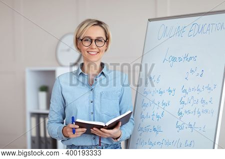 Portrait Of Happy Young College Teacher Standing Near Blackboard With Mathematics Problems, Conducti