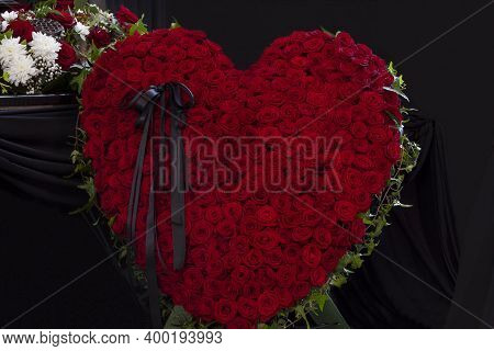 A Large Wreath Of Red Roses In The Shape Of A Heart With A Black Mourning Ribbon At The Funeral. Clo