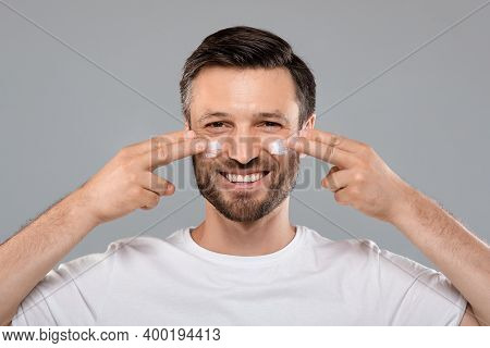 Smiling Handsome Man Applying Anti-aging Cream On His Face, Closeup. Middle-aged Bearded Man With Cr