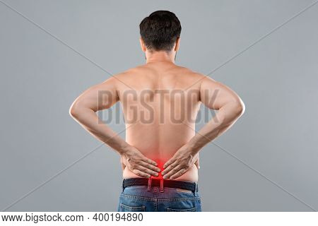 Unrecognizable Man Holding His Hands Behind His Back, Pain In Spine, Inflamed Zone Highlighted In Re