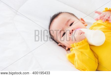 Asian Beautiful Little Baby Girl Wearing A Yellow Dress Eat Milk Sleeping Feeding Lying On The White