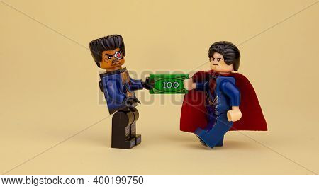 Ukraine, Kyiv - April 6, 2020: Lego Minifigures. Superman Gives A Hundred Dollars. Get Paid In Cash.