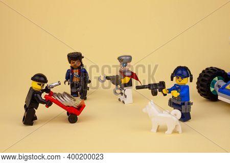 Ukraine, Kyiv - April 6, 2020: Lego Robber With A Gun Takes Away Coins On A Wheelbarrow. Lego Man Mi
