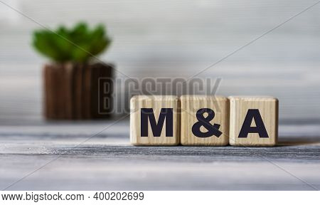 M&a (mergers And Acquisitions) - Word On Wooden Cubes Against The Background Of A Light Board With B