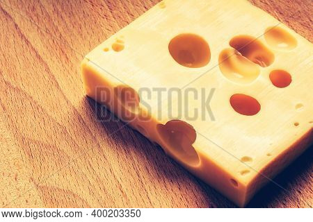 Swiss Yellow Cheese Square Chunks With Holes On Wood Board. Fresh Piece Of Cheese.