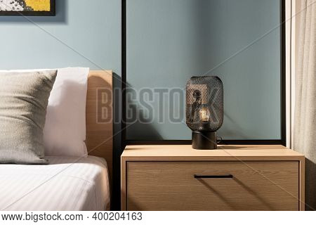 Closeup Of Modern Black Metal Edison Bulb Lamp On Wooden Bedroom Night Table In Contemporary Style G