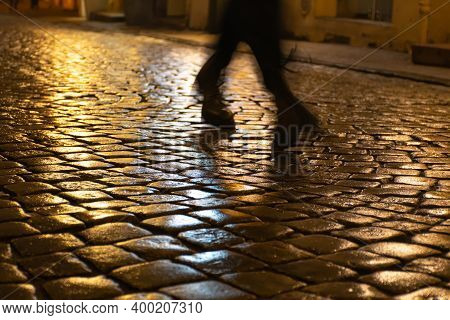 Wet Cobblestones At Night After Rain On A Street Or Road Surface, Bottom View With Shadow Or Silhoue