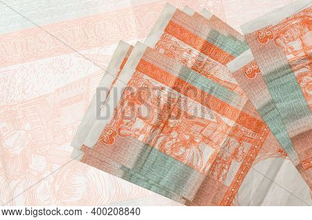 3 Cuban Pesos Convertibles Bills Lies In Stack On Background Of Big Semi-transparent Banknote. Abstr
