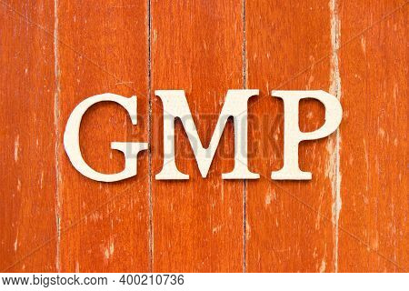 Alphabet Letter In Word Gmp (abbreviation Of Good Manufacturing Practice) On Old Red Color Wood Plat