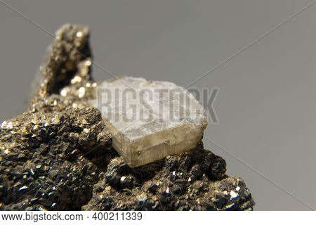 Rhombic Crystal Of Slightly Pinkish White Calcite That Grows Alongside Smaller Chalcopyrite Crystals