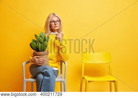 Indoor Shot Of Serious Blonde Middle Aged Woman Sits Alone On Chair Holds Poted Cactus Thinks About