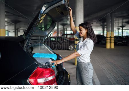 Young woman puts suitcases into the car on parking
