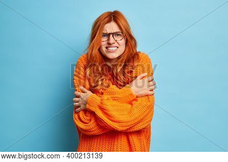 Redhead Woman Trembles From Cold Hugs Herself To Warm Up Walks Outdoor During Freezing Temperature C