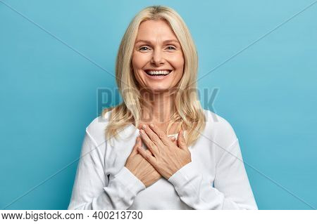 Photo Of Tender Blonde Woman With Wrinkles And Blonde Hair Keeps Hands Pressed To Chest Being Sincer