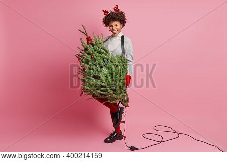 Full Length Shot Of Dark Skinned Woman Wears Red Reindeer Horns Carries Fir Tree Decorated With Garl