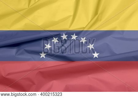 Fabric Flag Of Venezuela. Crease Of Venezuelan Flag Background, Yellow Blue And Red With An Arc Of E