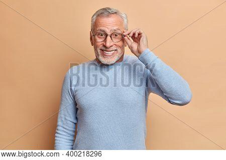 Portrait Of Cheerful Mature Man Pensioner Keeps Hand On Rim Of Eyeglasses Smiles Broadly Has White P