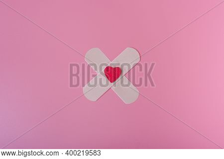 Medical Patch And Heart On A Pink Background.