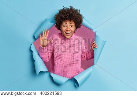 Happy Curly Haired African American Woman Waves Palm And Greets Friend Expresses Positive Emotions D