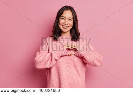 Attractive Brunette Young Asian Woman Feels Happy And Romantic Shapes Heart Gesture Expresses Tender