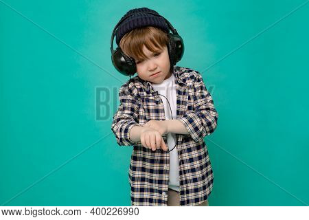 Small Stylish Boy, A 4-5-year-old Kid In A Plaid Shirt And A White T-shirt With A Cap On His Head Da