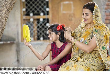 Joyful Girl With Mother Having Fun Looking Into Handheld Mirror