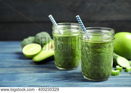 Delicious Fresh Green Juice On Blue Wooden Table. Space For Text