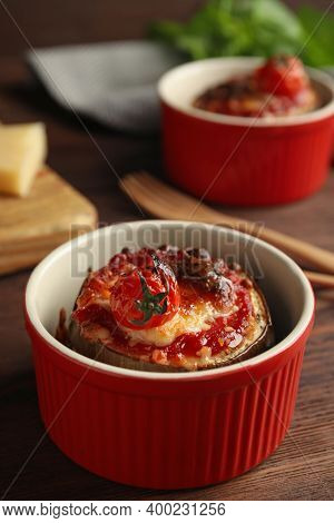 Baked Eggplant With Tomatoes And Cheese In Ramekin On Wooden Table, Closeup